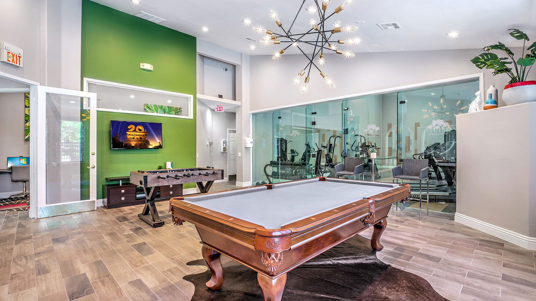 Spacious community entertainment and game room with pool table, foosball table, and flat-screen TV. Behind this area is the fitness center, separated by a glass wall.