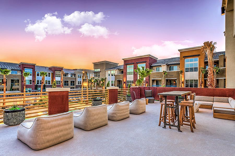 Outdoor dining and lounge terrace overlooks the resort-style community pool in the center of apartment buildings.